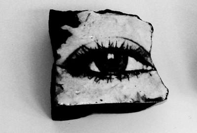 Femme fossile, autoportrait : Un bloc, grès noir et chromo 15 x 15 cm